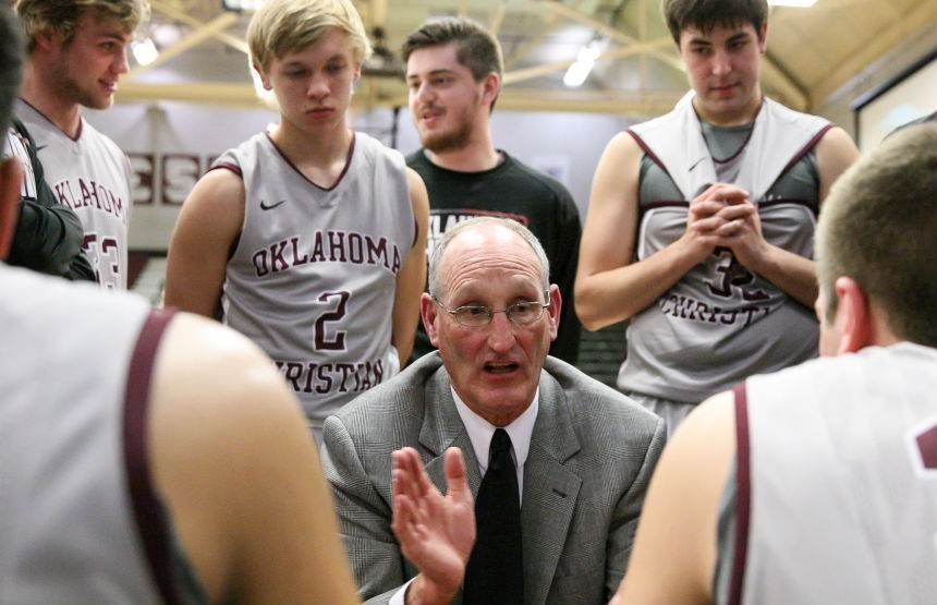 OC men's basketball coach Dan Hays (center) speaks to his team during a timeout during a December game against Manhattan Christian (Kan.). Hays is resigning after 33 years as the Eagles' coach. Photo courtesy of OCEagles.com