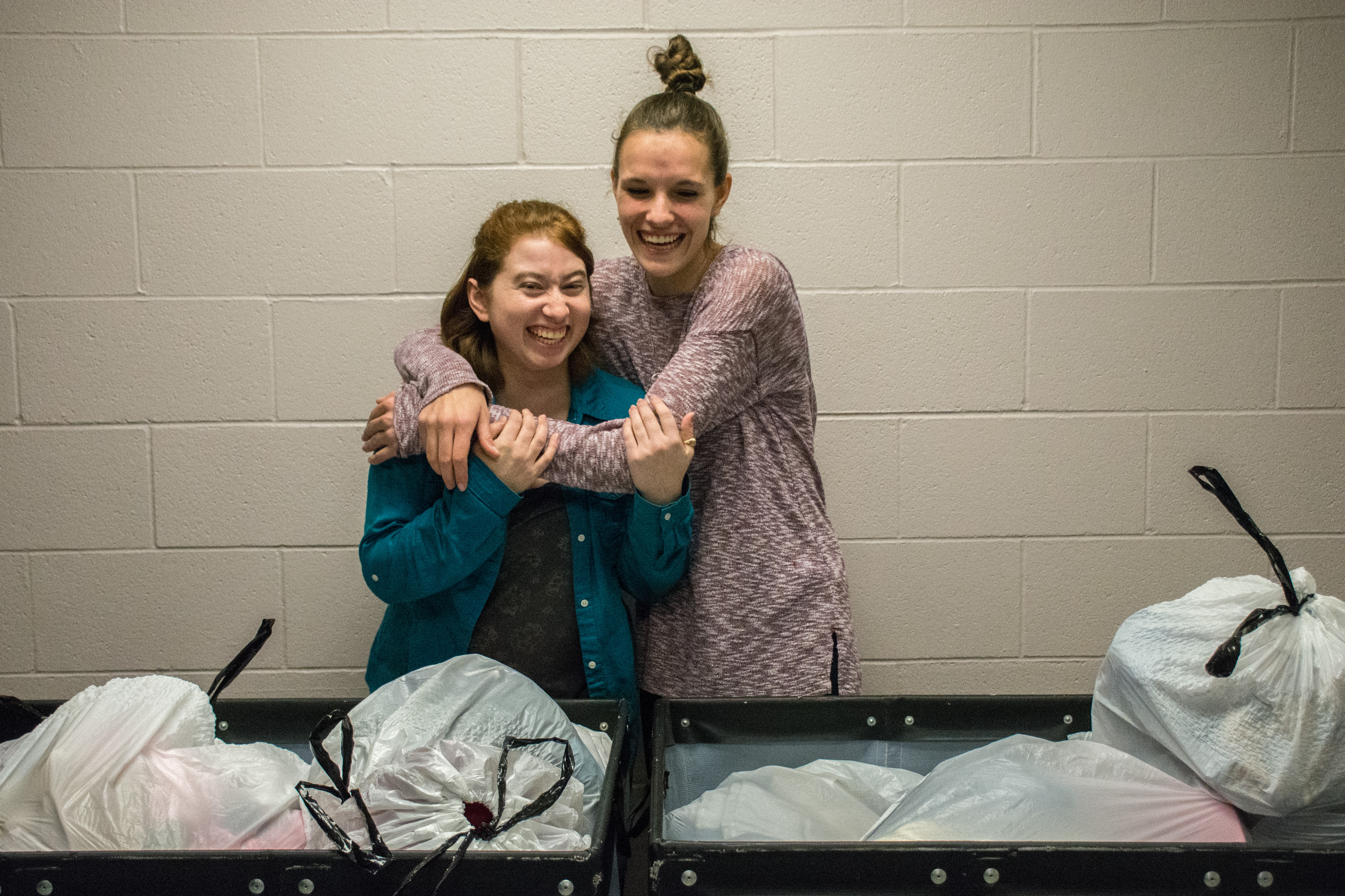 Students Monica Hamrin (left) and Anna Hurst (right), stand over piles of clothes donated to their project to help the homeless in the Oklahoma City metro area.  Photo by Abby Bellow