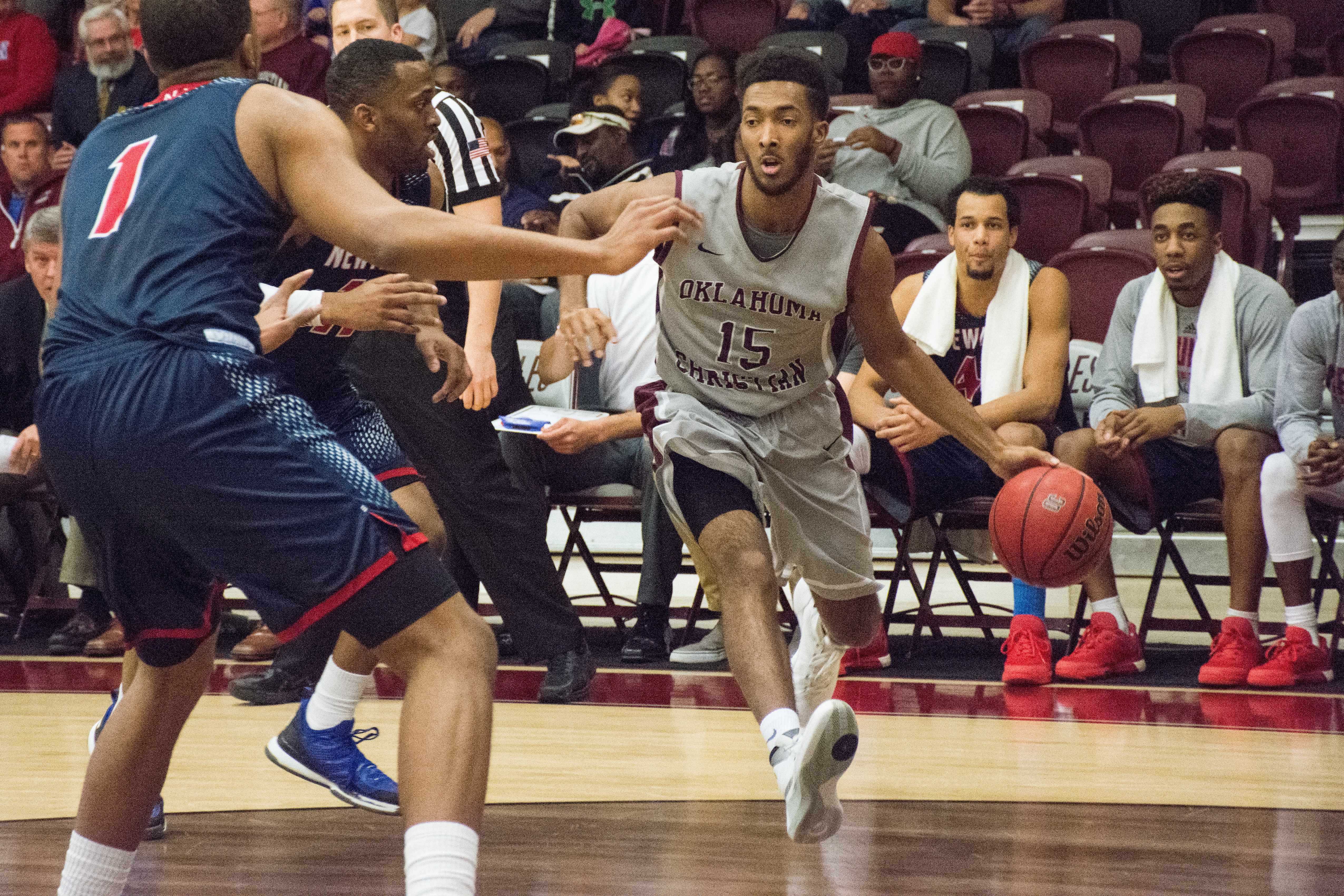 Elijah Strickland works his way around Newman University defenders on Feb. 11. Photo by Abby Bellow.