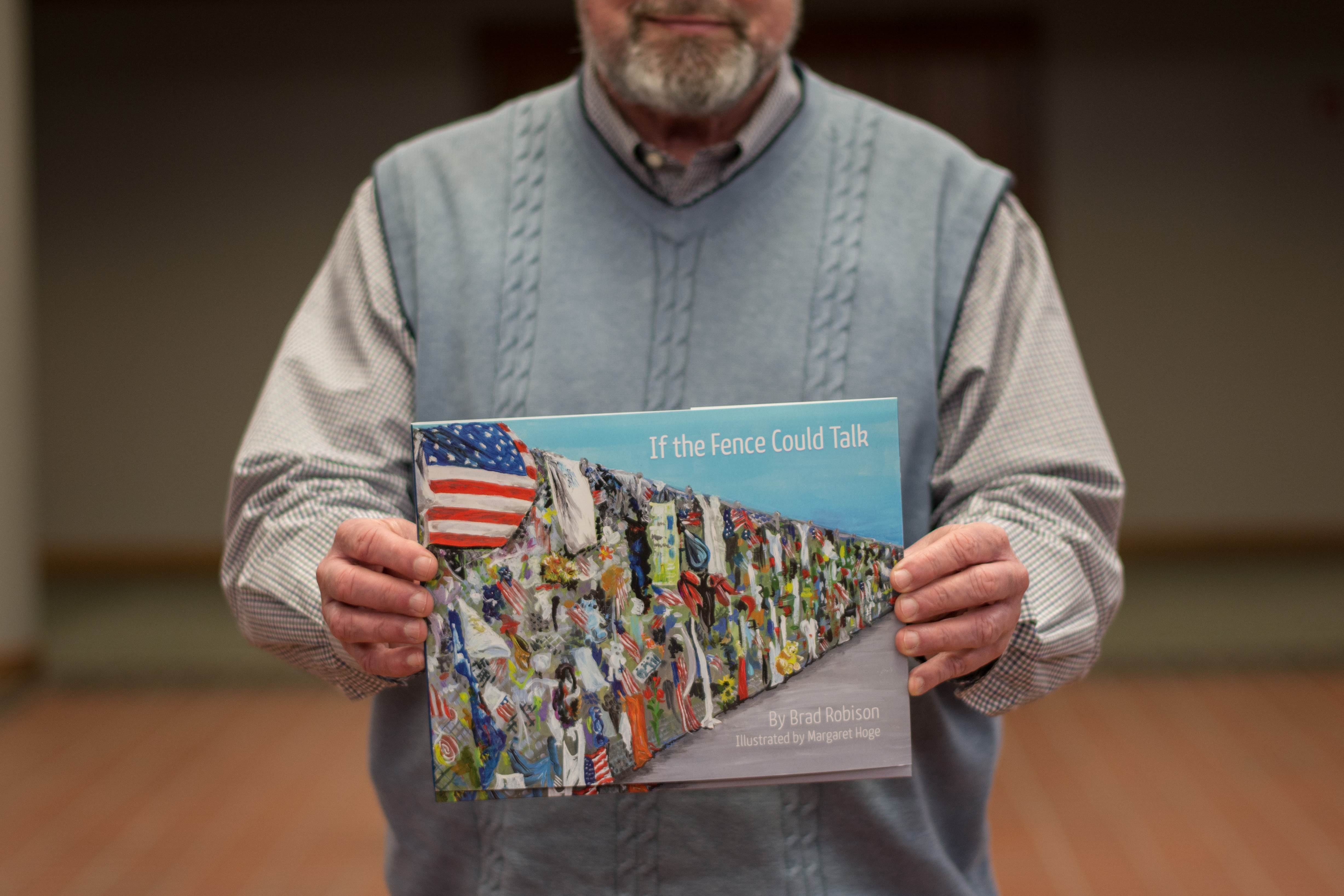 "Brad Robison, former Oklahoma Christian librarian, holds his book ""If The Fence Could Talk."" Photo by Abby Bellow."