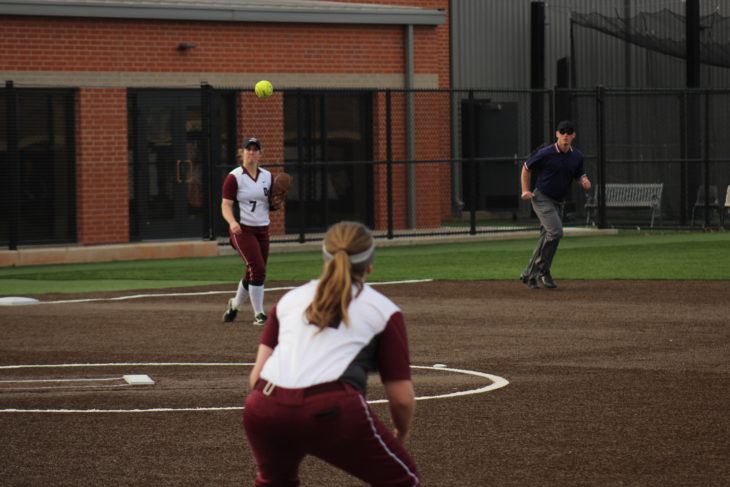 Sophomore Bridget White throws the ball to first baseman Madison Nordyke. Photo by Jenny Rigney.
