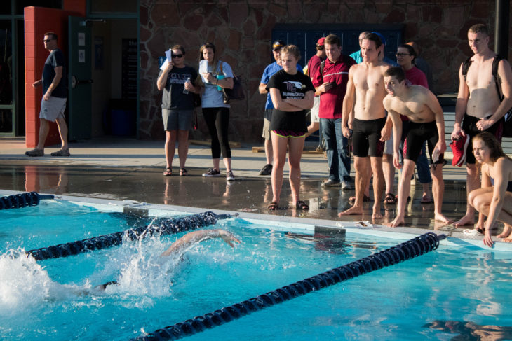 Eagle swimmer makes the turn in a race while teammates cheer. Photo by Jenny Rigney