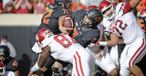 Oklahoma State's Mason Rudolph gets tackled during Bedlam loss. Online image