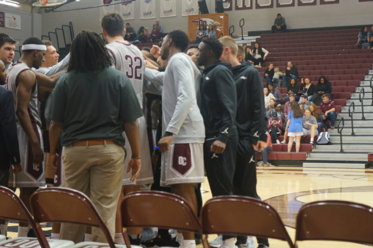 The men's basketball team discusses the team plan. Photo by Elise Miller